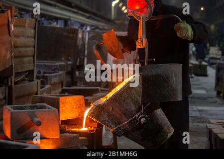Industrial chill casting. The process of for filling out mold with molten metal from ladle. - Stock Photo
