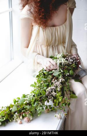 Crop woman in elegant white wedding dress with big bouquet of small white flowers and green foliage standing among transparent pastel color curtains