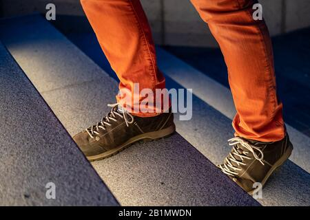Male legs in walking boots and red jeans climb the illuminated stone steps on a winter evening. Close-up. - Stock Photo