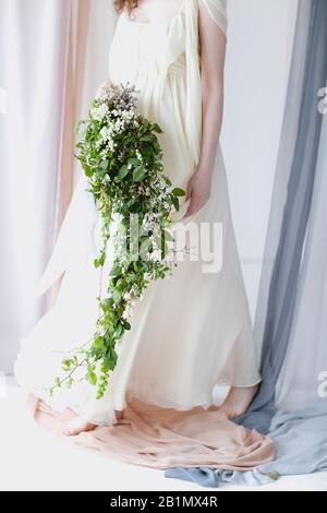 Crop barefoot woman in elegant white wedding dress with big bouquet of small white flowers and green foliage standing among transparent pastel color c