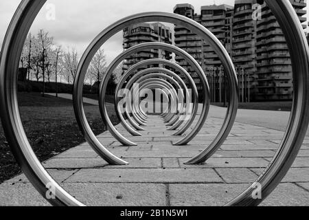 Bicycle inox ring rack in the city park of Citylife, Milan, Italy, with residential buildings and trees in the background - Stock Photo