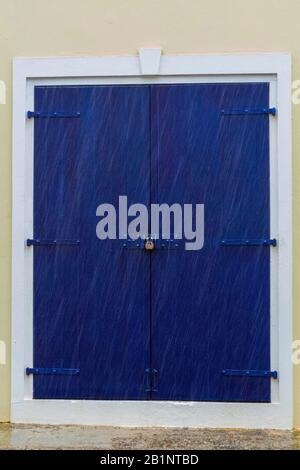 Caribbean shop door, Under lock and key, Blue door with white trim, virgin islands weathered architecture, locked wooden door, padlocked building - Stock Photo