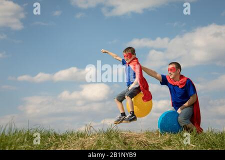 Father and son playing superhero at the day time. People having fun outdoors.They jumping on inflatable balls on the lawn. Concept of friendly family. - Stock Photo