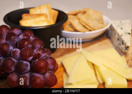Selection of cheese served with crackers and fresh sweet red grapes on a wooden table. Food background. No people. Copy space - Stock Photo