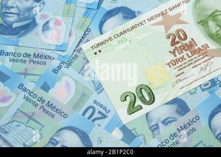 A close up image of a green twenty Turkish lira bank note on a background of Mexican twenty peso bank notes in macro - Stock Photo