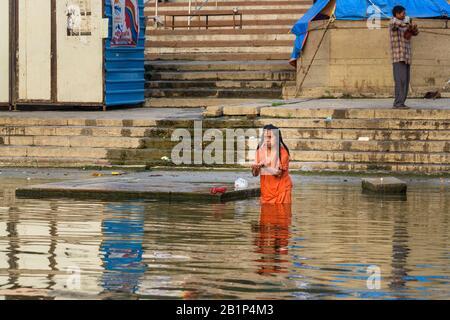 Indian elderly woman bathing in water holy Ganga river in morning. Varanasi. India - Stock Photo