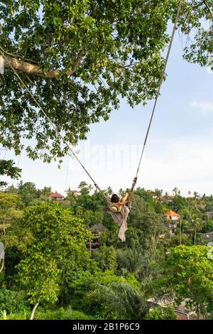 Female flying on swing above jungles stock photo - Stock Photo