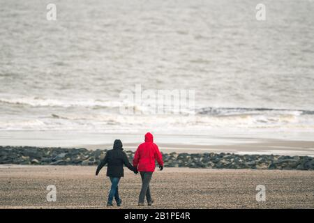 27 February 2020, Lower Saxony, Norderney: A winterly dressed couple goes for a walk on the North Sea beach of Norderney in the morning when it is cold. Photo: Mohssen Assanimoghaddam/dpa - Stock Photo