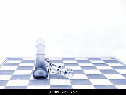 Two King chess pieces on a board in red - Stock Photo