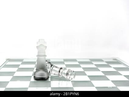 Two King chess pieces on a board in grey - Stock Photo