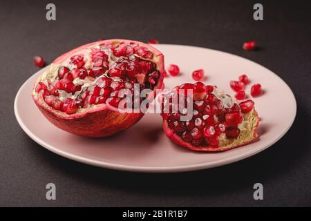 Fresh tasty sweet peeled pomegranate with red seeds in pink plate on dark black background, angle view, healthy food fruits - Stock Photo