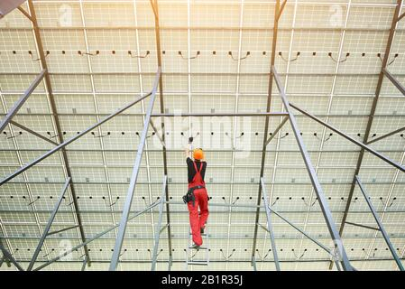 Installing and wiring of solar photo voltaic panels. Back view of worker in orange uniform connecting solar panels at the station. Ecology power conservation concept.