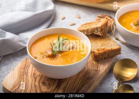 Homemade Autumn Butternut Squash pumpkin cream Soup with Bread and seeds. top view