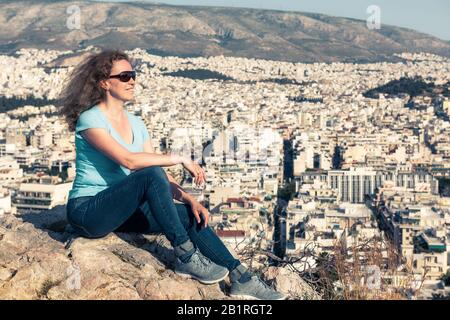 Pretty young woman relax overlooking the Athens cityscape, Greece. Smiling female tourist sits on the top of hill in Athens center in summer. - Stock Photo