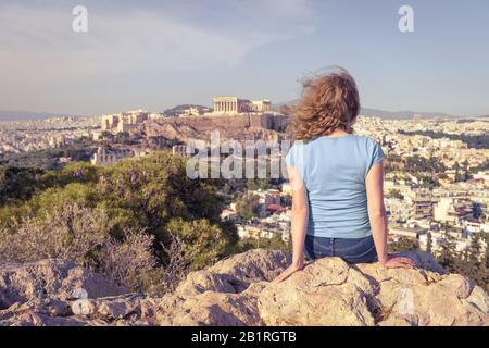 Young woman looks at cityscape of Athens, Greece. Adult girl tourist relaxes on hill top overlooking Acropolis of Athens in summer. Scenic view of Ath - Stock Photo