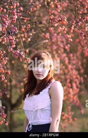 Girl stands under plum tree, portrait, - Stock Photo