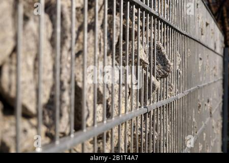 Close-up of a wall detail made of a gabion. Gabion filled with granite. - Stock Photo