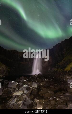 Northern lights over Gufufoss waterfall, East Iceland. - Stock Photo