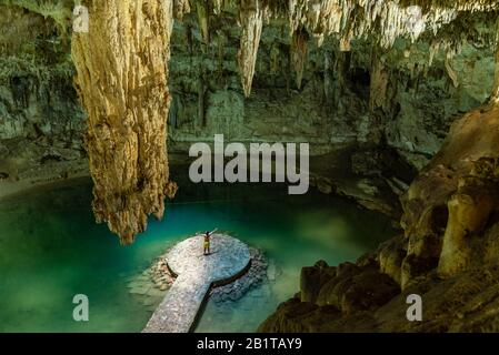 Man enjoying the view of Suytun Cenote from the top Yucatan Mexico North America