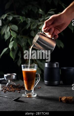 Male hand pours milk from metal pitcher into transparent glass with black coffee on dark surface and green tree leaves background