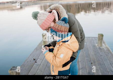 mom looking at pictures on a camera with her son outside in winter - Stock Photo