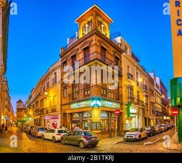 SEVILLE, SPAIN - OCTOBER 1, 2019: The beautiful historical corner house with tower and popular cafeteria on the ground floor, on October 1 in Seville - Stock Photo
