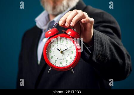 Bearded businessman in suit holding red alarm clock. Time management concept