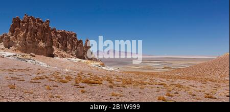 The wind-eroded Cathedrals of Tara, with the Salar de Tara (Tara Salt Flat) and Andes Mountains in the distance, Atacama Desert, Chile - Stock Photo