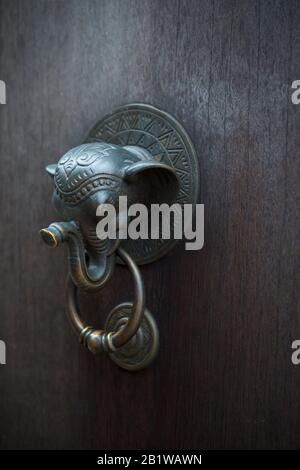 Buddhist Ganesha elephant door knocker on dark wooden door. Ganesha is revered as the remover of obstacles. Welcome home. Shallow DOF. - Stock Photo