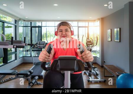 fat woman training on exercise bike in gym calories
