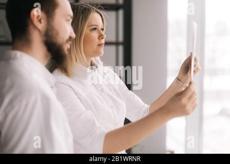 Medical team of two young doctors discuss X-ray of patient in meeting room - Stock Photo