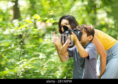 Little boy taking photo with her mother in the woods.