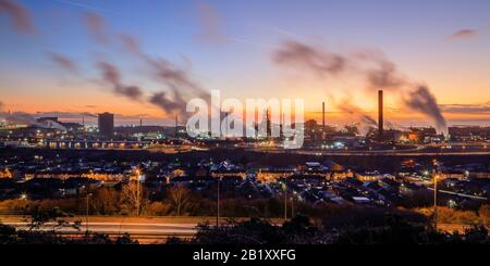 Overview of Port Talbot steel works emitting clouds of steam in the evening light Port Talbot Swansea Glamorgan Wales