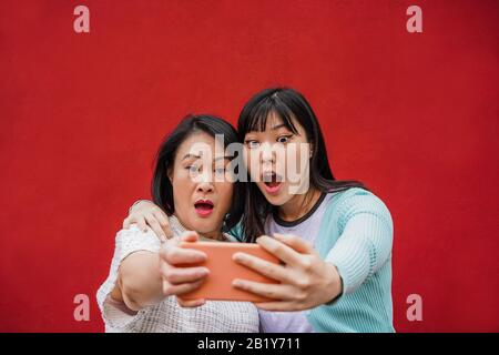 Asian mother and daughter shocked looking videos on smartphone - Happy family people having fun with technology trends - Love, parenthood lifestyle, t