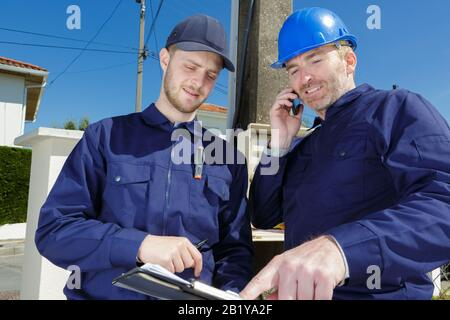 electician with substation on the background - Stock Photo