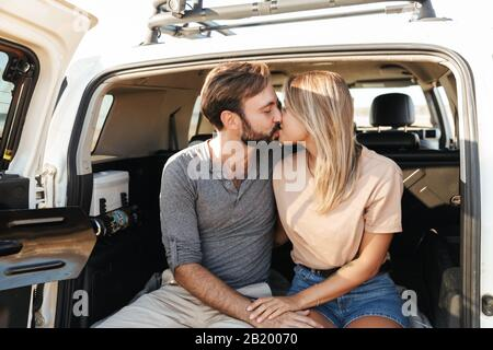 Image of a cute young amazing loving couple outdoors hugging in car at the beach kissing. - Stock Photo