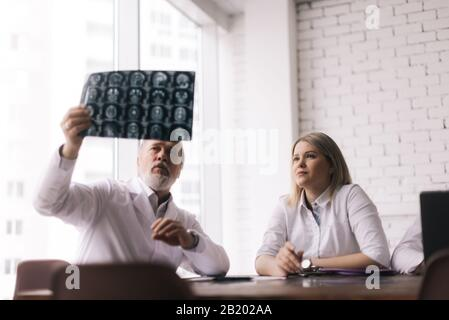 Team of three doctors discuss X-ray of patient in consulting room of hospital - Stock Photo