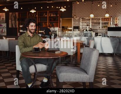 Happy caucasian young man sitting in cafe using mobile phone Stock Photo