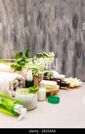 Healthy and beauty spa flower concept. Natural ingredients for relaxation. Mint salt, olive soap, green tea essential oil, towels, shower gel. Stone c - Stock Photo