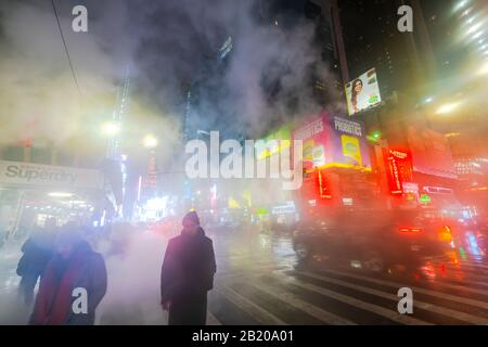 The drifting steam surrounds the people, traffic and Times Square buildings in the snowy night at Midtown Manhattan New York City NY USA on Jan. 2020. - Stock Photo