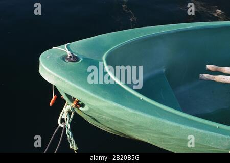 A close up view of the bow of green rowing boat just showing the handle ends of the oars and the mooring ropes against dark blue sea water