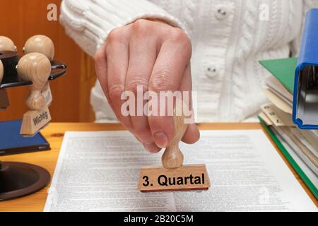 a stamp wit the inscription 3. Quartal (3rd quarter) is hand-held - Stock Photo