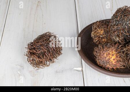 Lot of whole old brown rambutan with brown ceramic coaster on white wood - Stock Photo