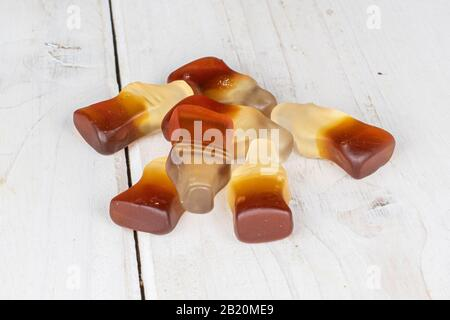 Lot of whole sweet jelly cola on white wood - Stock Photo