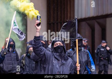 London, UK. 28th Feb, 2020. Anarchist protesters march towards the Stock Exchange with smoke flares. Various anarchist and anti capitalist groups rally at the Bank of England before moving on to blockade the Stock Exchange in Paternoster Sq. The groups are against what they see as wilful destruction of Earth's ecosystems and the capitalist system supporting this process. Penelope Barritt/Alamy Live News - Stock Photo