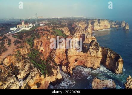 Aerial panoramic photo view of Ponta da Piedade headland with group of rock formations yellow-golden cliffs along limestone coastline, Lagos, Portugal - Stock Photo
