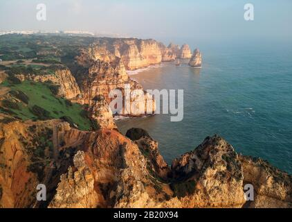 Aerial panoramic view of Ponta da Piedade headland with group of rock formations yellow-golden cliffs along limestone coastline, Lagos, Portugal - Stock Photo
