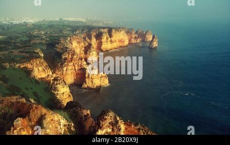 Aerial image above view of Ponta da Piedade headland with group of rock formations yellow-golden cliffs along limestone coastline, Lagos Portugal - Stock Photo