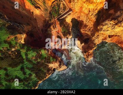 Aerial photo above view Ponta da Piedade headland with group of rock formations yellow-golden cliffs along limestone coastline, Lagos Portugal - Stock Photo