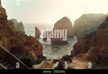 Above view of Ponta da Piedade headland with group of rock formations yellow-golden cliffs along limestone coastline, Lagos town,Portugal - Stock Photo